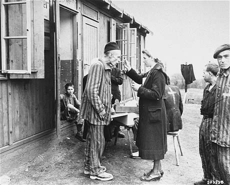 A sick Polish survivor in the Hannover-Ahlem subcamp receives medicine from the Red Cross, 11 April 1945